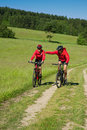 Summer - Young couple riding bike in a meadow Stock Photo