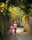 Summerfun two cute girls running in alley in summer carefree and having fun Royalty Free Stock Images
