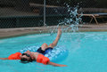 Boy in pool floating kicking Royalty Free Stock Photo