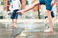 Summertime enjoyment kids legs in fountain and feet wet outdoors Royalty Free Stock Photo