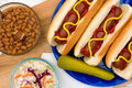 Summertime hotdogs grilled with summer time sides on a picknic table Royalty Free Stock Photos
