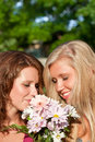 Summertime two girls smelling flowers in the sunshine Royalty Free Stock Images