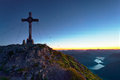 Summit cross on mountain with lake in valley at sunrise Stock Photography