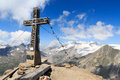 Summit cross and prayer flag on mountain Kreuzspitze with glacier panorama and Grossvenediger, Hohe Tauern Alps, Austria Royalty Free Stock Photo