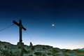 Summit cross on stony rocky mountain with stars and moon Royalty Free Stock Image