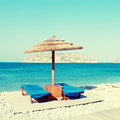 Sun beds and umbrellas on the beach of mediterranean sea crete greece square toned image instagram effect Stock Photo