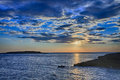 Sun behind clouds above sea level in sunset time Royalty Free Stock Photo