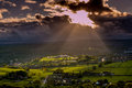 Sun breaking out of clouds small town under filtered sunlight Stock Photography