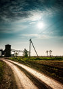 Sun and clouds over field with road. Royalty Free Stock Photo