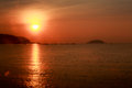 Sun disk among red sky fishing boats on horizon at sunrise Royalty Free Stock Photo