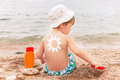 The sun drawing sunscreen on baby boy back suntan lotion caucasian child is sitting with plastic container of and toy Royalty Free Stock Image