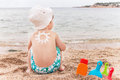 The sun drawing sunscreen on baby boy back suntan lotion caucasian child is sitting with plastic container of and toys Royalty Free Stock Image