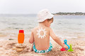 The sun drawing sunscreen on baby (boy)  back. Royalty Free Stock Photo