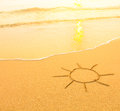 Sun drawn in the sand of a beach, soft surf wave. Travel. Royalty Free Stock Photo