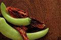 Sun dried tomatoes green peppers on a cutting board wooden Stock Images