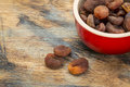 Sun dried turkish apricots in a stoneware bowl on a grunge painted wood surface Royalty Free Stock Image