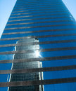 Sun flair reflection off glass skyscraper with other building reflecting and Stock Photo