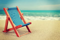 Sun lounger in sandy beach vintage toned vacation background with Royalty Free Stock Photo