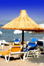 Sun loungers by the beach on a mediterranean coast Royalty Free Stock Images