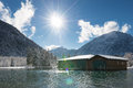 Sun over boat house at sunny and snowy winter day Royalty Free Stock Photo