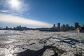 Sun over frozen city up high a partially river in montreal Royalty Free Stock Photo