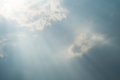 Sun projecting rays behind dramatic clouds in the blue sky before a thunderstorm Royalty Free Stock Photo