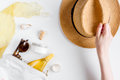 Sun protection cosmetic cream with beach outfit on white background top view