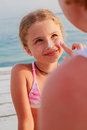 Sun protection mother anoints her daughter face protective cream on the beach Royalty Free Stock Photography