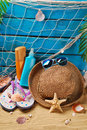 Sun protection still life on the beach with suntan lotion bottles straw hat sunglasses flip flops and shells Royalty Free Stock Photos