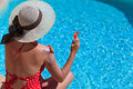 Sun protection on summer vacation woman putting solar cream shoulder near the pool Stock Photography