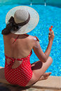 Sun protection on summer vacation woman putting solar cream shoulder near the pool Stock Photo