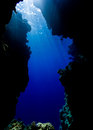 Sun rays filter down through blue water in a sea cave Stock Photos