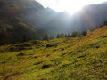 Sunlight into high alpine valley at fall