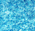 Sun reflection on the blue clear water ripples of swimming pool with mosaic bottom Royalty Free Stock Photography