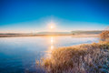 Sun rises over the river autumn frost frozen covered with thin ice grass covered with sunrise sunset Royalty Free Stock Photos
