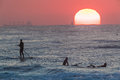 Sun rising horizon sup riders surfing telephoto lens photo of surfers on dawn patrol with and surfboards watching the rise over Stock Image