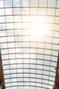 The sun`s rays shine through the glass roof of the shopping center. Beautiful modern architectural background. Blue cloudy sky and Royalty Free Stock Photo