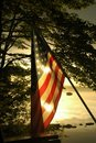 Sun Sets Behind American Flag Stock Photo