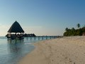 Sun sets down on a maldive s island pavilion white sand beach and sea at sunset time Stock Photography
