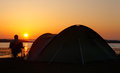 Sun sets horizon behind camper sitting relaxing enjoying his camping holiday creating silhouette pitched tent him sitting Royalty Free Stock Images