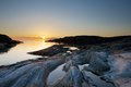 The sun sets out in the north sea along a rocky coast line Royalty Free Stock Image
