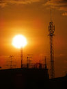 Sun setting behind a silhouetted electricity pylons Royalty Free Stock Photo