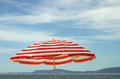 Sun shade red and white beach umbrella over blue sky Stock Photography