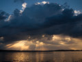 The sun shines through the clouds over lake Royalty Free Stock Photos