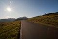 Sun shining on the road through mountain plateau valdresflye jotunheimen norway Stock Photos