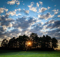 Sun shining through trees at sunset. Dramatic cloudy sky. Green countryside Royalty Free Stock Photo