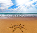 Sun sign drawn on sand of beach tropical and sunlight Royalty Free Stock Image