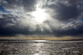 Sun through the stormy clouds at the frozen sea with broken ice Stock Image