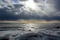 Sun through the stormy clouds at the frozen sea with broken ice Royalty Free Stock Photography
