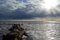Sun through the stormy clouds at the frozen sea with broken ice Stock Photo